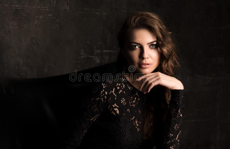 Dark horizontal portrait of a woman in a black lace dress. Professional makeup. Dark horizontal portrait of a woman in a black lace dress. Professional make-up royalty free stock photos