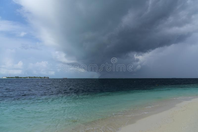 Dark hurricane cloud above tropical sea stock image