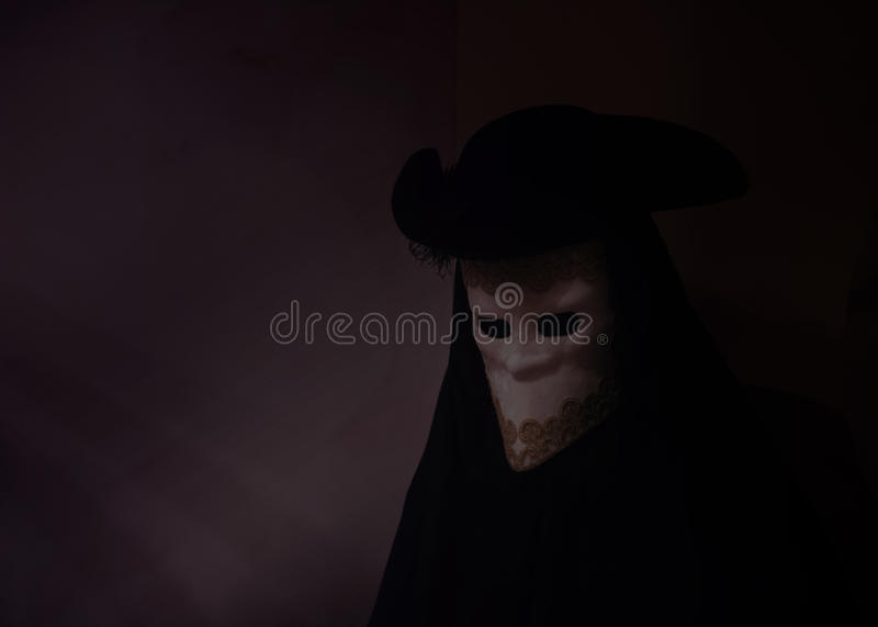 Dark image of person in venetian bauta costume. Dark and mysterious photo of a person dressed in the venetian masquarade costume called bauta. The white face royalty free stock image
