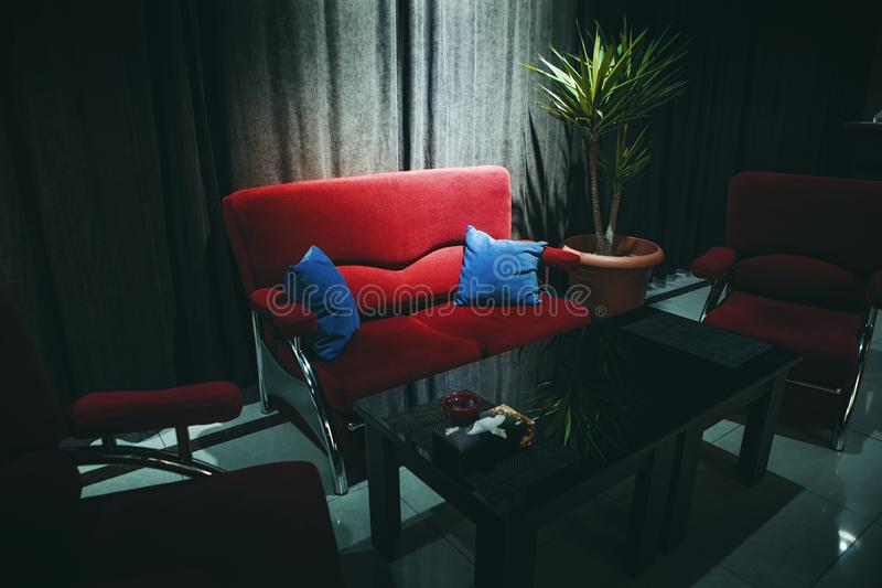 Dark interior with a red sofa. And light royalty free stock images
