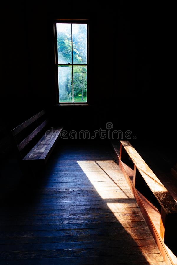 Dark interior of a small church in the countryside. A dark interior of a small church in the countryside with sunlight shining and visible nature in the window stock photo