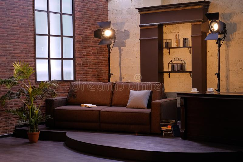 Dark interior with window, sofa, floor lamps, flower in a pot. royalty free stock images