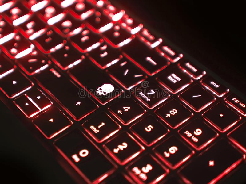 Dark keyboard with red backlight and skull key stock image