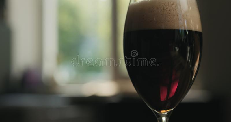 Dark lager beer into a glass backlit by sunset light stock images