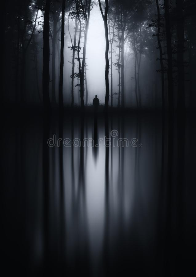 Dark lake reflection in haunted forest. Man reflecting in lake in mysterious dark haunted forest. Dark fantasy forest with fog. Haunted Halloween forest with royalty free stock photo