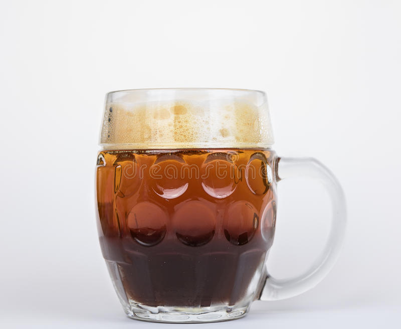 Dark and light beer in mug. stock photos