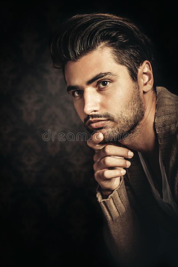 Dark light portrait of a young handsome man, hand under his chin. stock images