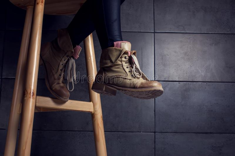 Low section of woman wearing boots sitting at bar counter in cafe. Dark low section of woman wearing boots sitting at bar counter in cafe stock image