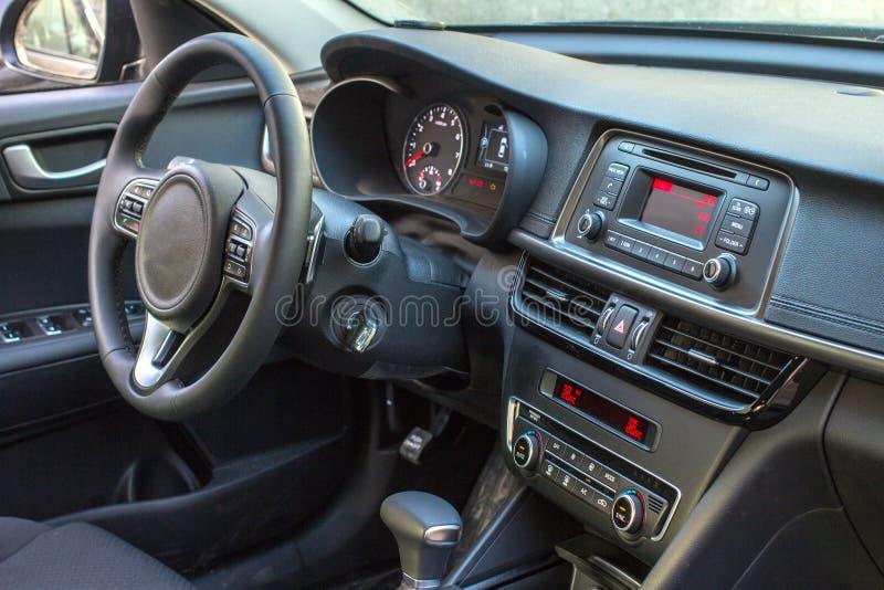 Dark luxury car Interior - steering wheel, shift lever and dashboard royalty free stock photo