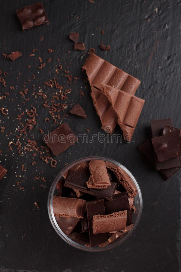 Dark and milk chocolate bars and pieces on black stone board. Sweets and desserts concept stock photos