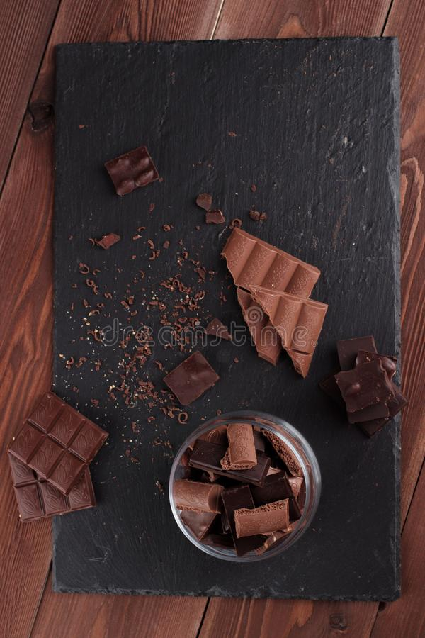 Dark and milk chocolate bars and pieces on black stone board. Sweets and desserts concept stock photo