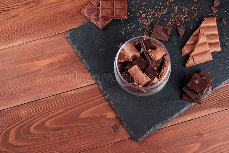 Dark and milk chocolate bars and pieces on black stone board. Sweets and desserts concept royalty free stock photography
