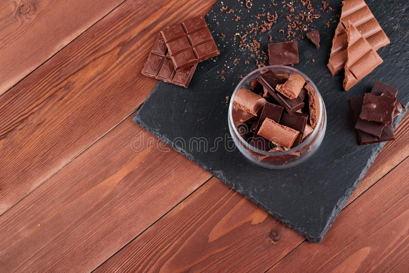 Dark and milk chocolate bars and pieces on black stone board. Sweets and desserts concept stock photography