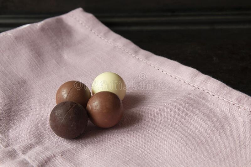 Dark, milk and white chocolate pralines on pink linen close up side view with copy space royalty free stock photography