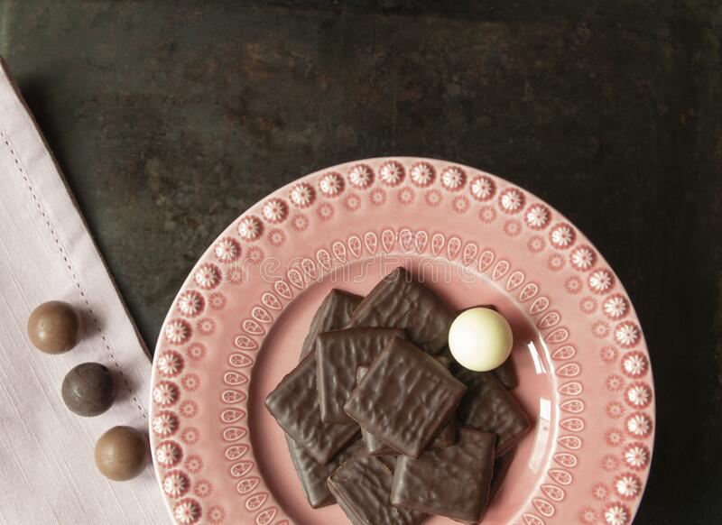 Dark, milk and white chocolate rectangles and pralines on pink plate and linen with rustic dark background stock photography