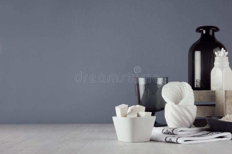 Dark minimalistic bathroom decor - dark glass vase, wood box, towel, products and accessories for care face skin on white wood. stock photos