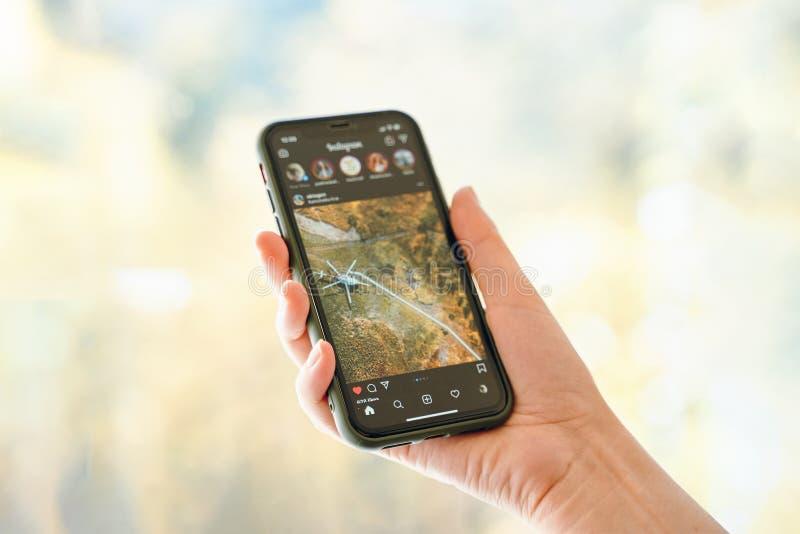 Dark mode instagram. Bishkek, Kyrgyzstan - October 8 2019: Woman holds iphone 11 in dark mode with instagram app open royalty free stock image