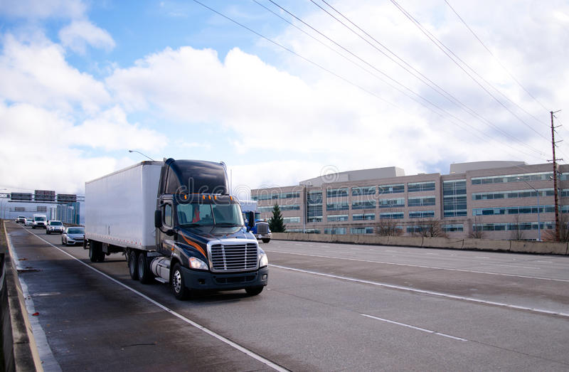 Dark modern day cab semi truck dry van trailer. Modern dark rig day cab semi truck with spoiler on top with a dry van trailer is moving in front of column of royalty free stock photos
