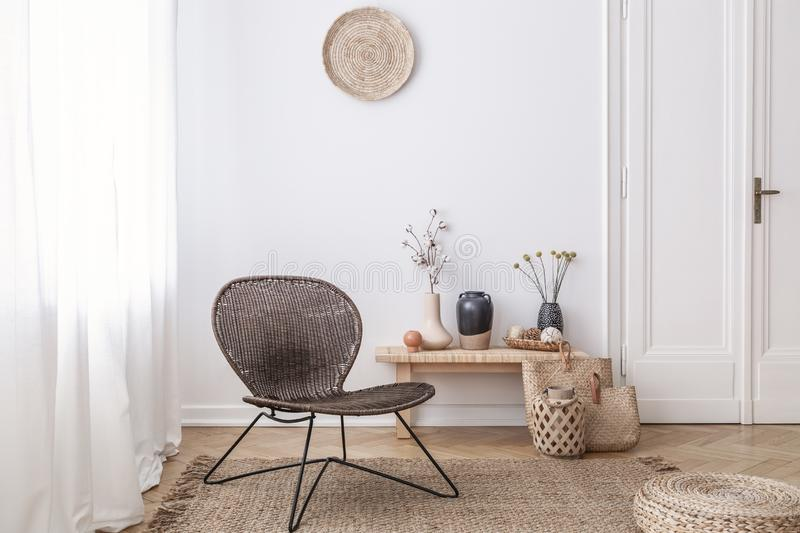 Dark, modern wicker chair in a white living room interior with a wooden bench and decorations made from natural materials royalty free stock images