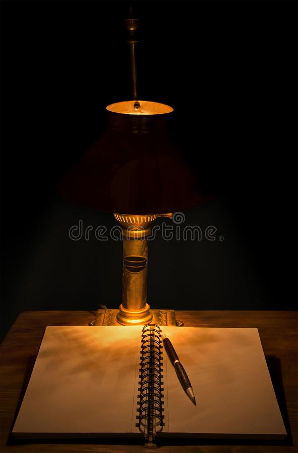 Dark, moody image of an open journal with a pencil on a wooden table stock photo