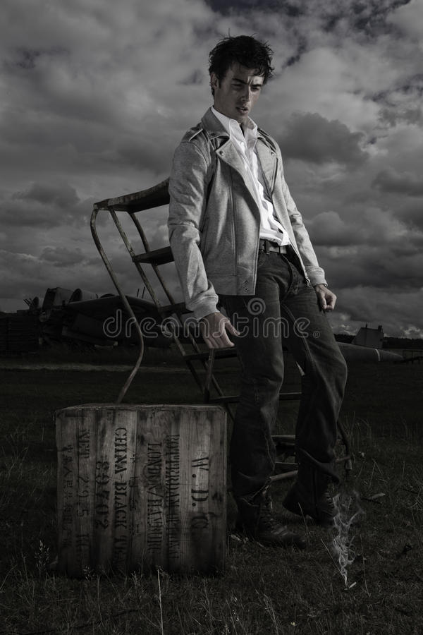 Dark moody image of young man. Dark moody image of a young man in a casual jacket standing alongside a vintage crate under a threatening stormy sky stock images