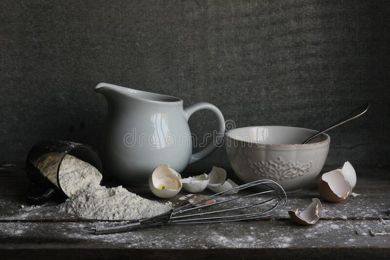 White Porcelain Jug And White Porcelain Bowl With A Metal Egg Whisk Lying Around And Some Eggshells And Flour Scattered Around On stock photo