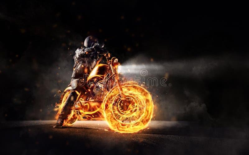 Dark motorbiker staying on burning motorcycle royalty free stock photos