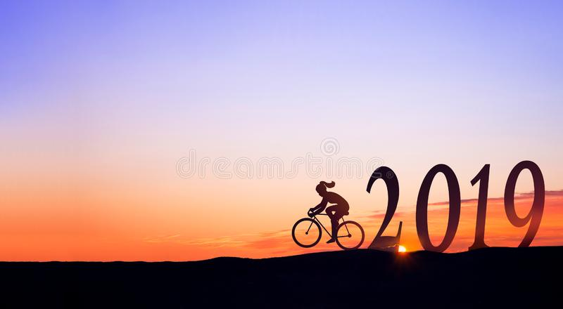 2019 On dark mountains with silhouette of a woman biking and sunrise as background. 2019 On dark mountains with silhouette of a woman biking and sunrise as stock images