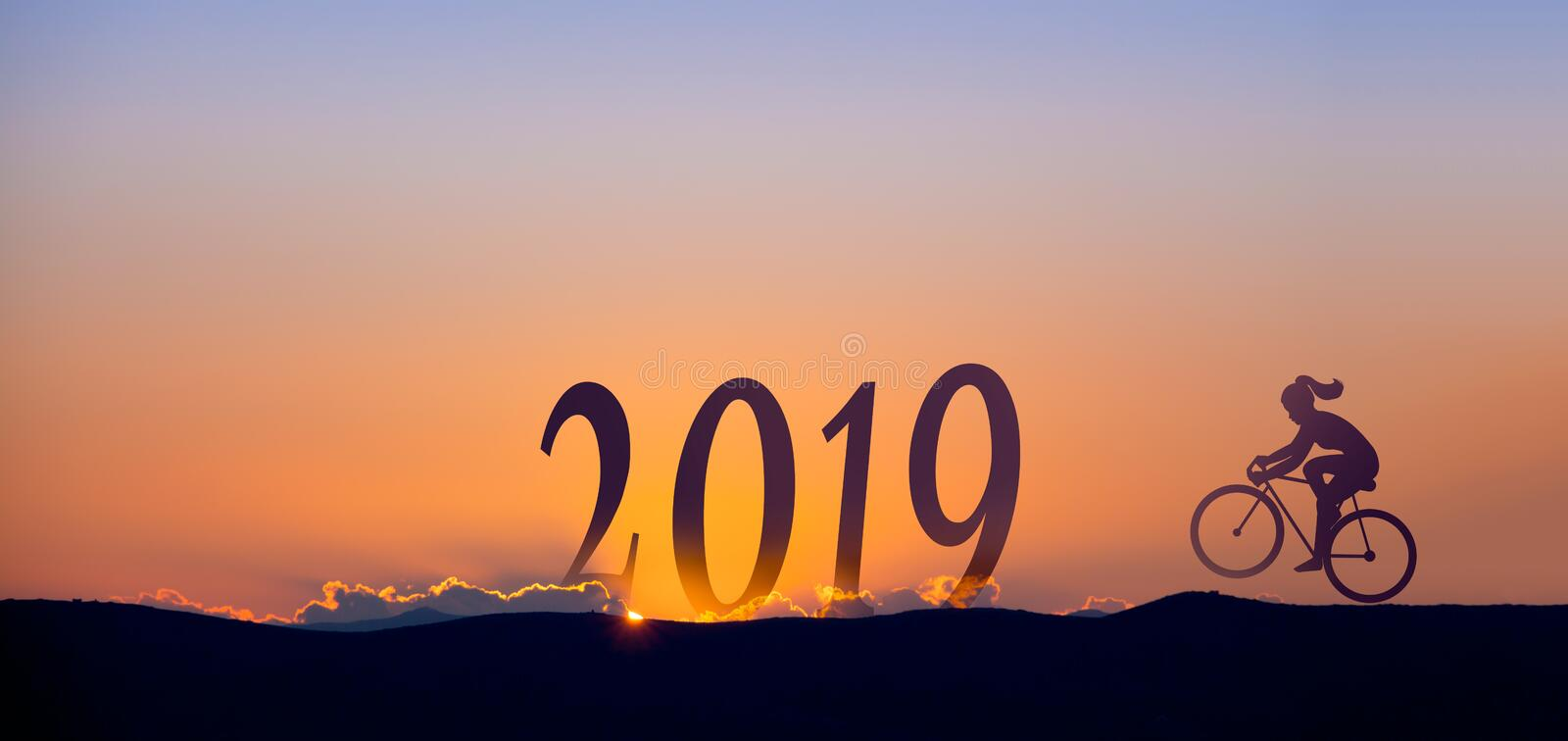 2019 On dark mountains with silhouette of a woman biking and sunrise as background. 2019 On dark mountains with silhouette of a woman biking and sunrise as stock photos