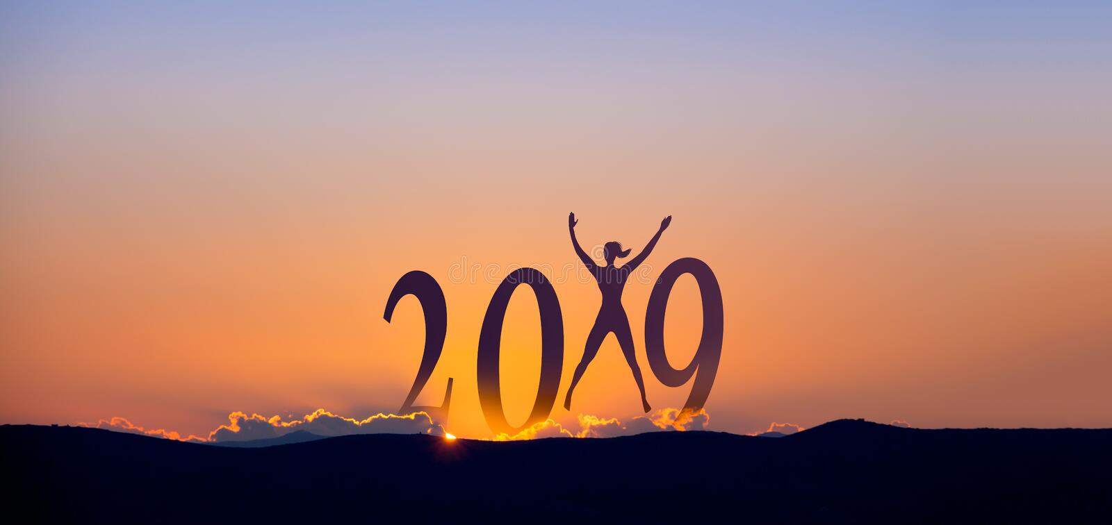 2019 On dark mountains with silhouette of a woman jumping in the air and sunrise as background. 2019 On dark mountains with silhouette of a woman jumping in the royalty free stock photos