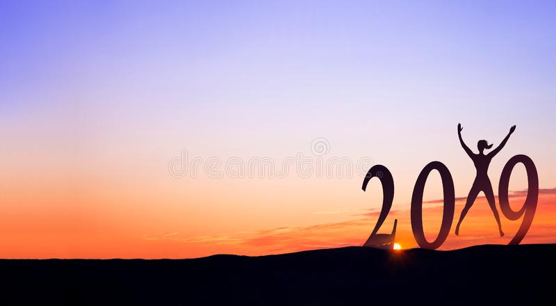 2019 On dark mountains with silhouette of a woman jumping in the air and sunrise as background. 2019 On dark mountains with silhouette of a woman jumping in the stock photos