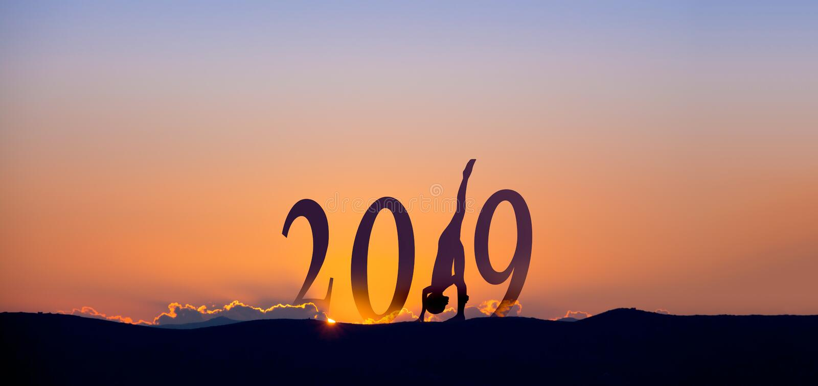 2019 On dark mountains with silhouette of a woman practicing yoga and sunrise as background. 2019 On dark mountains with silhouette of a woman practicing yoga stock photography