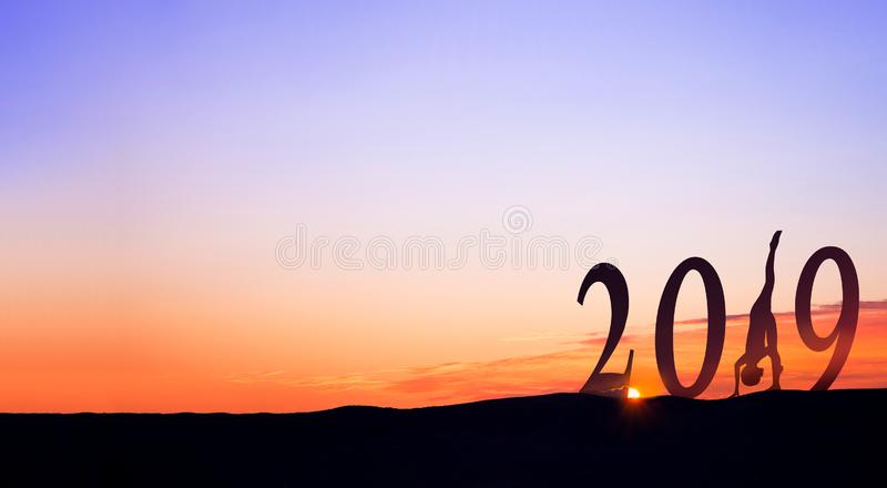 2019 On dark mountains with silhouette of a woman practicing yoga and sunrise as background. 2019 On dark mountains with silhouette of a woman practicing yoga stock image