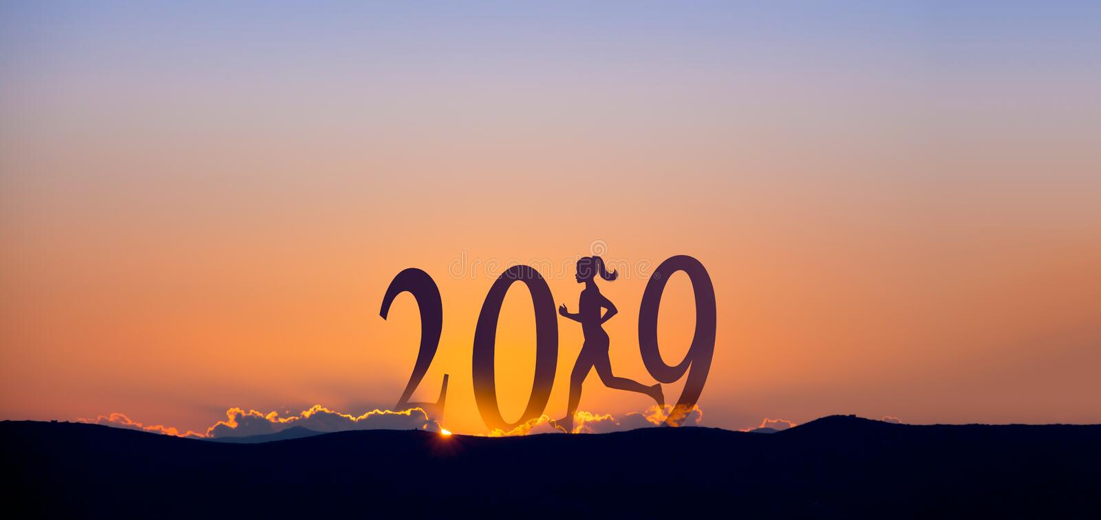 2019 On dark mountains with silhouette of a woman running and sunrise as background. 2019 On dark mountains with silhouette of a woman running and sunrise as royalty free stock photography