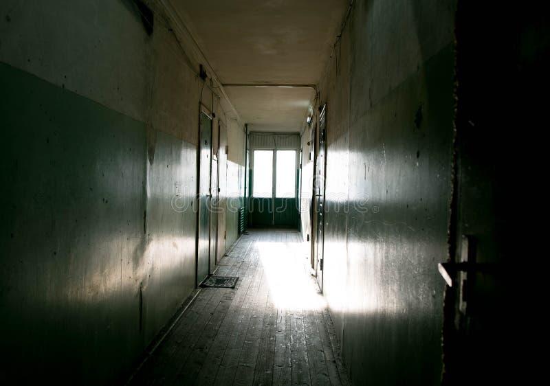 Dark mysterious corridor in building. Door room perspective in lonely quiet building with dramatic light. Horror landscape concept. Creepy Doors royalty free stock image