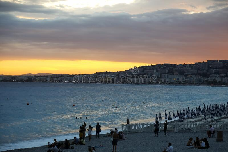 Dark night arrives in Nice. Nice, France - September 24, 2018: Dark night arrives at Cote d`azur, The Bay of Angels. There are people still on the beach and the stock image