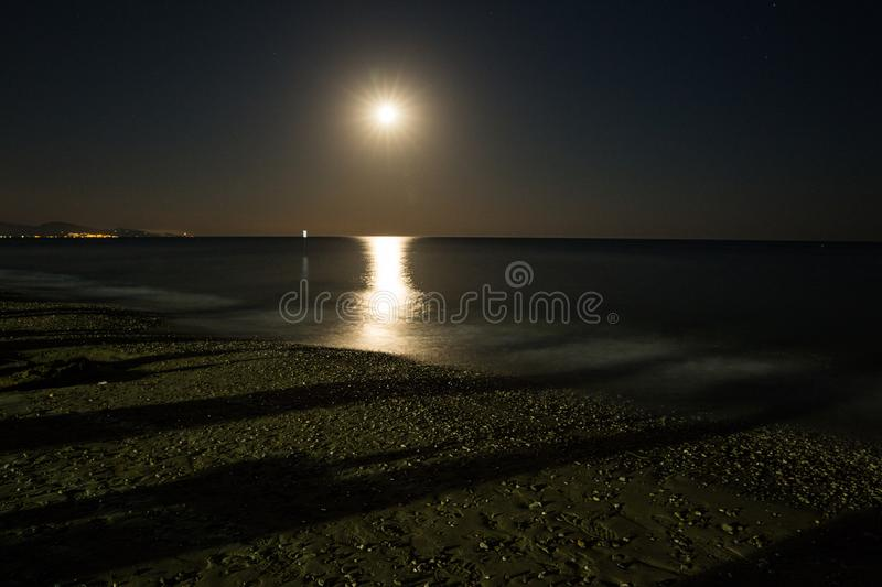Full moon shines on beach stock photography