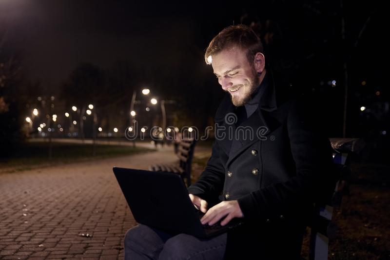 Dark night, one smiling young man, 20-29 years, sitting on bench alone, using his laptop in public park in Autumn.  royalty free stock photo