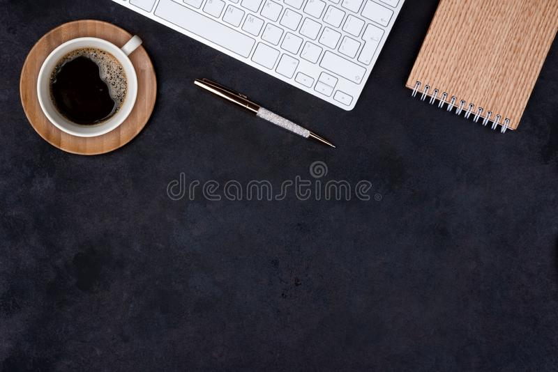 Dark office table top view with coffee cup and keyboard royalty free stock photography