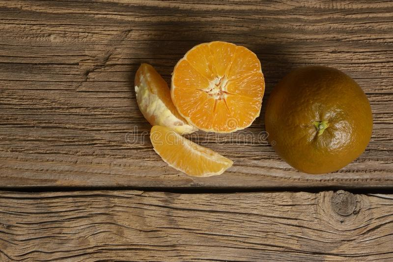 Dark orange isolated on wooden background. Brown oranges stock photography