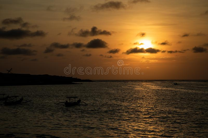 Dark orange sunset view over the beach with a boat in Bali stock photography
