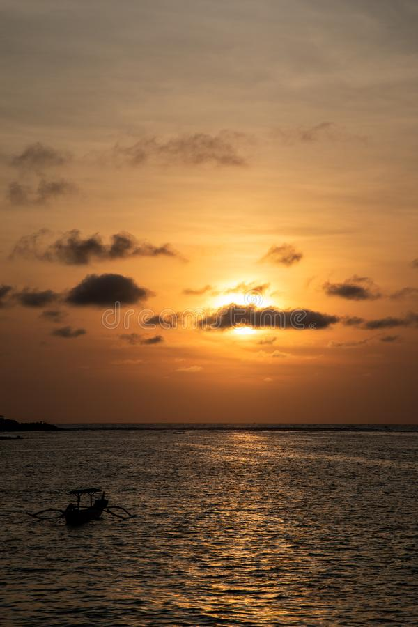 Dark orange sunset view over the beach with a boat in Bali royalty free stock image