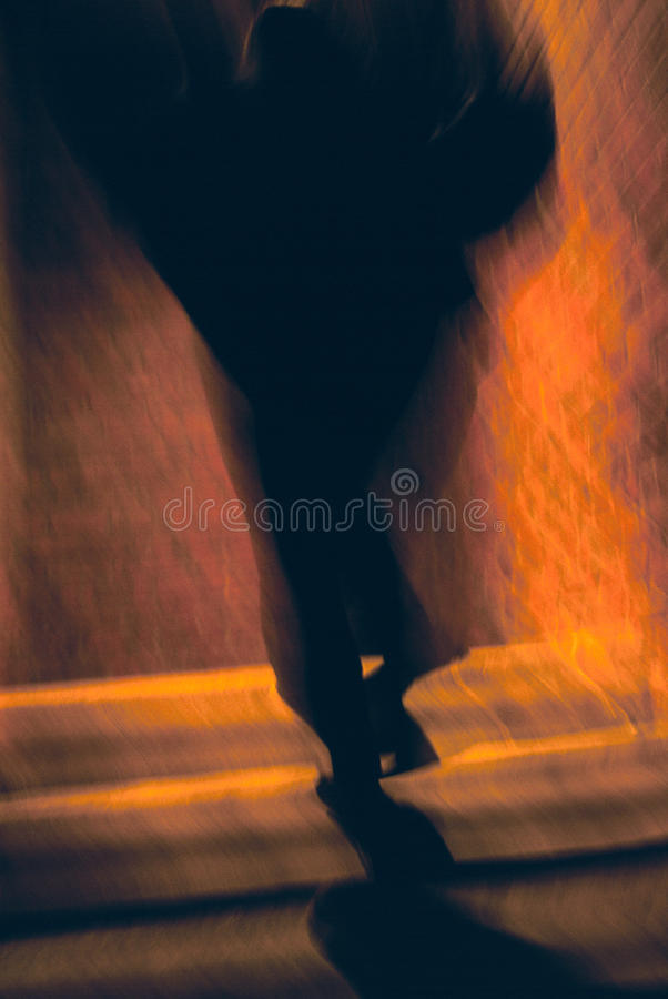 Dark Outline On Stairway. A dark outline of legs and a torso blurs as it ascends the stairs into a brick building stock photo