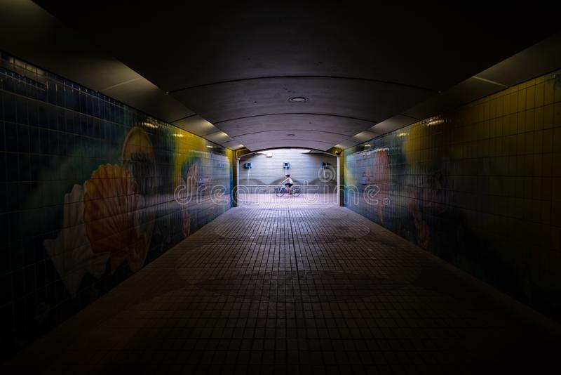 Dark pedestrian tunnel with one motion blurred cyclist, Abu Dhabi stock image