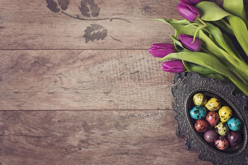 Dark photo of Easter quail eggs in an ancient metal bowl. Beautiful spring flowers - purple tulips on a wooden background. Floral stock photography