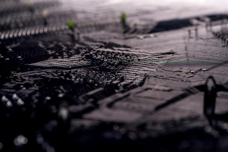 Dark photo of motherboard downside. Close-up view stock photos