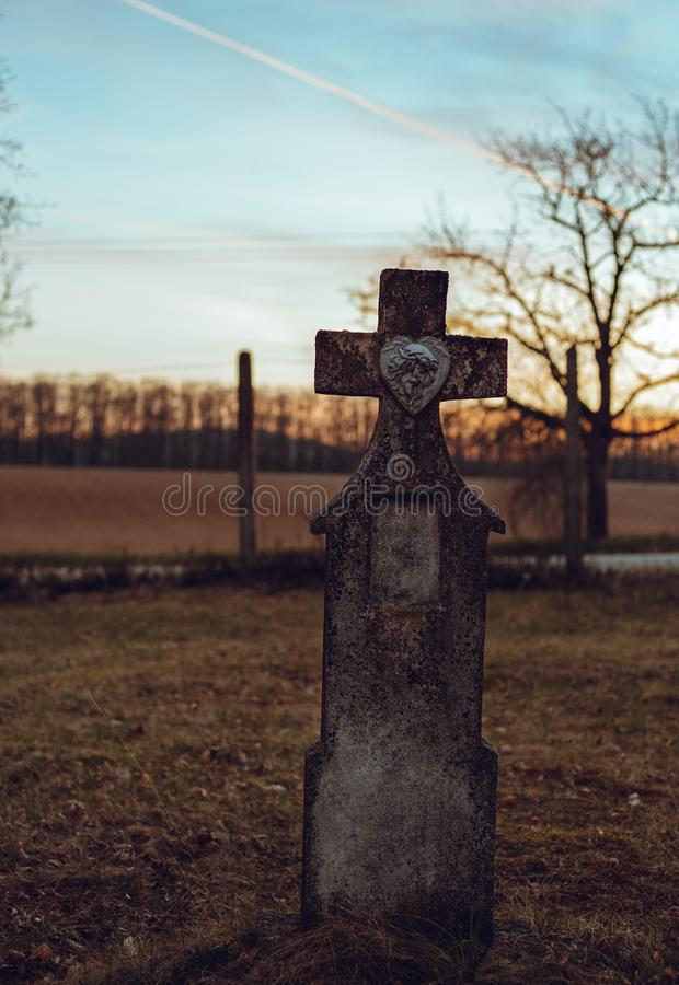 Dark photo of old and abandoned cross grave stone on European cemetery with tree and forest on background on sunset. Creepy and royalty free stock photography