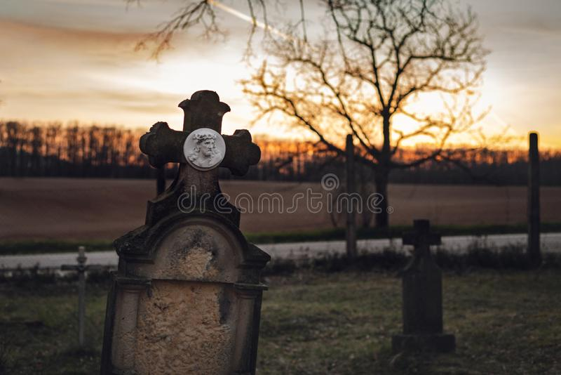 Dark photo of old and abandoned cross grave stone on European cemetery with tree and forest on background on sunset. Creepy and. Illuminated tombstones on royalty free stock photos