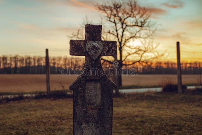 Dark photo of old and abandoned cross grave stone on European cemetery with tree and forest on background on sunset. Creepy and. Illuminated tombstones on royalty free stock image