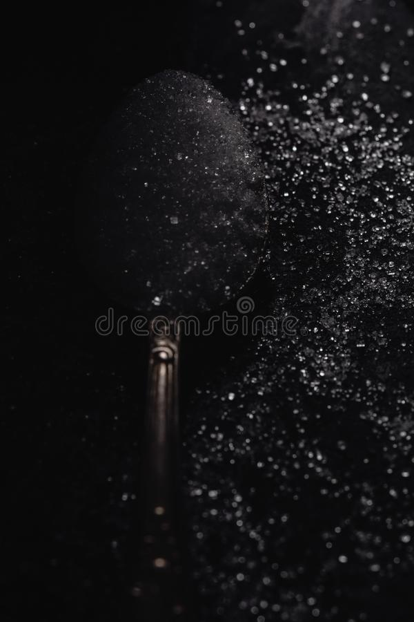 A dark photo of a spoon with white sugar on a black stone background with copy space, top view, low key lighting stock image